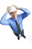 Man wearing hardhat frowning, hands on head - Asia Images Group