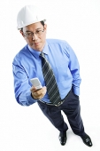 Man wearing hardhat looking at mobile phone - Asia Images Group
