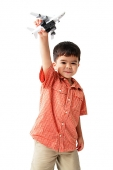 Boy standing and holding toy airplane, looking at camera - Asia Images Group