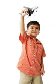Boy holding toy airplane, playing - Asia Images Group