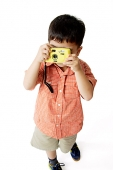 Boy standing and looking through camera - Asia Images Group