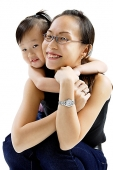 Mother and daughter embracing, smiling at camera - Asia Images Group