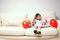 Young girl sitting on sofa, looking at camera - Asia Images Group