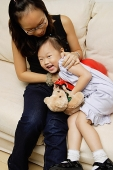 Mother and daughter on sofa, daughter smiling  at camera - Asia Images Group