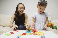 Mother and daughter, playing with toys, smiling - Asia Images Group