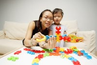 Mother and daughter looking at toy pieces - Asia Images Group
