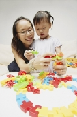 Mother and daughter playing with puzzle pieces - Asia Images Group