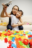 Mother and daughter playing toy airplane - Asia Images Group