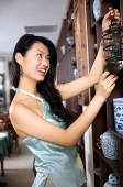 Woman in shop, looking at birdcage - Asia Images Group