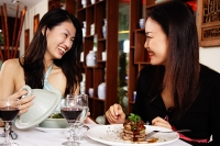 Women in restaurant, sitting at table with food - Asia Images Group