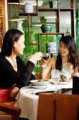 Two women eating in restaurant, toasting with drinks - Asia Images Group
