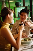 Couple dining in Chinese restaurant, toasting with wine glasses - Asia Images Group