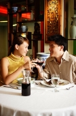 Couple toasting with wine glasses in Chinese restaurant - Asia Images Group