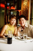 Couple having dinner in Chinese restaurant, smiling at camera - Asia Images Group
