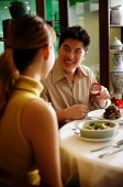 Man proposing to woman at restaurant - Asia Images Group