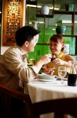 Couple toasting with wine glasses in restaurant - Asia Images Group