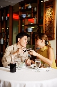 Couple sitting face to face in Chinese restaurant, toasting with wine glasses - Asia Images Group