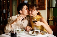 Couple in Chinese restaurant, holding wine glasses, man kissing woman on cheek - Asia Images Group