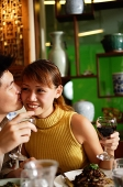 Man kissing woman on cheek in restaurant - Asia Images Group