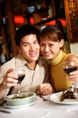 Couple in restaurant, smiling at camera, holding wine glasses - Asia Images Group