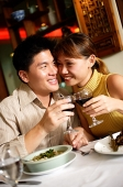 Couple in restaurant, sitting cheek to cheek, holding wine glasses - Asia Images Group