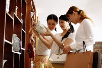 Three women studying teapot in antique shop - Asia Images Group