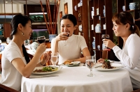 Women in restaurant, eating - Asia Images Group
