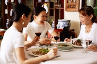 Women in restaurant, sitting at table, talking - Asia Images Group