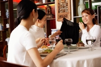 Three women in restaurant, one woman showing clothing item to the others - Asia Images Group