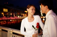 Couple standing face to face, woman holding single rose stalk - Asia Images Group