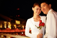 Couple standing side by side, woman holding single rose stalk, both looking at camera - Asia Images Group
