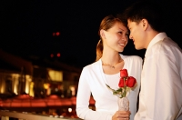 Couple standing face to face, woman holding single rose stalk, portrait - Asia Images Group
