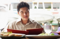 Man in cafe, looking at menu - Asia Images Group