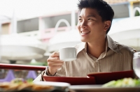 Man in cafe, menu in front of him, holding cup, looking away - Asia Images Group