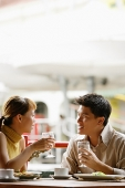 Couple in cafe, sitting side by side, holding glasses of water - Asia Images Group