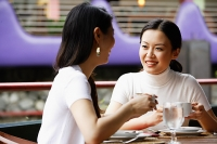 Women in cafe, drinks in hand, sitting at table - Asia Images Group