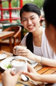 Women eating out, holding cups of coffee - Asia Images Group