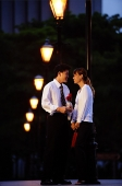 Couple standing face to face, man holding single rose stalk - Asia Images Group