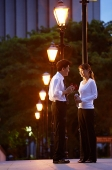 Couple standing face to face, under streetlights - Asia Images Group