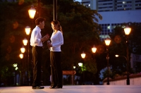 Couple standing face to face, rows of streetlamps behind them - Asia Images Group