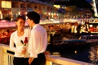 Couple standing next to railing, woman holding rose - Asia Images Group