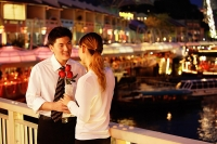 Man and woman standing face to face, woman holding roses - Asia Images Group