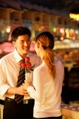 Couple standing face to face, woman holding roses - Asia Images Group