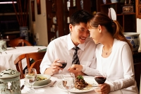 Couple in restaurant, sitting face to face - Asia Images Group
