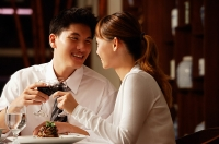 Couple in restaurant, sitting side by side, toasting with wine glasses - Asia Images Group