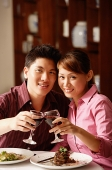 Couple in restaurant, toasting with wine glasses, looking at camera - Asia Images Group