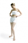 Young woman standing, holding tape measure around her waist - Asia Images Group