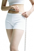 Woman holding tape measure around her mid-section - Asia Images Group