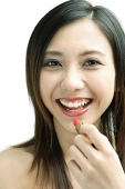 Woman smiling at camera, putting on lipstick - Asia Images Group