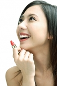 Woman smiling looking away, holding lipstick - Asia Images Group